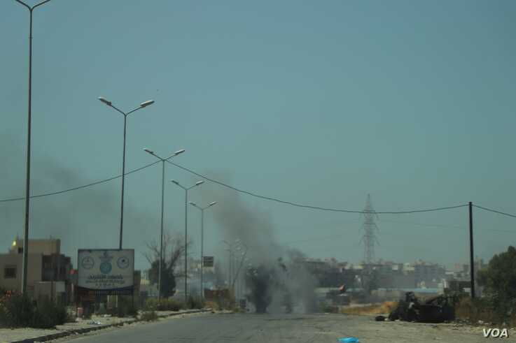A tank burns in the distance after being hit by an airstrike, July 7, 2019 in Tripoli, Libya. (Heather Murdock/VOA)