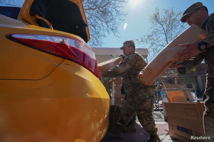 Members of the U.S. Army National Guard distribute boxes of free food provided by multiple New York City agencies, during the…