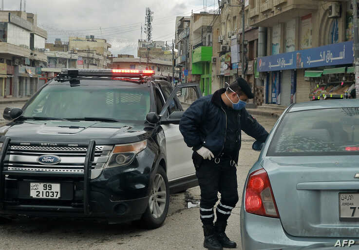 FILE - A policeman speaks to a driver of a car at a checkpoint during a nationawide coronavirus curfew, in the Jordanian capital Amman, March 21, 2020.