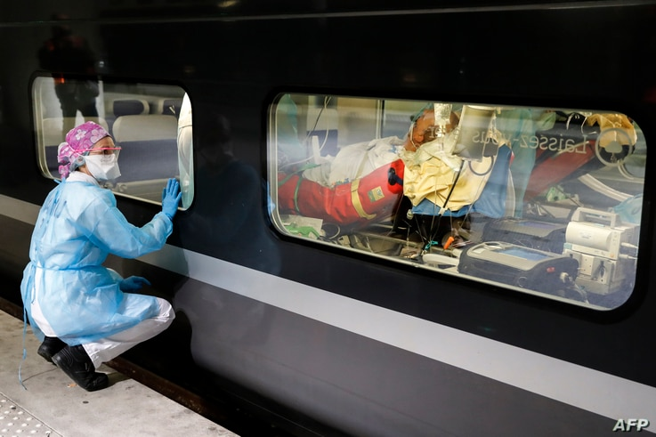 A medical staff watches through the window of a medicalized TGV high speed train at the Gare d'Austerlitz train station in Paris, France, before its departure to evacuate patients infected with the COVID-19 to hospitals in Brittany region.