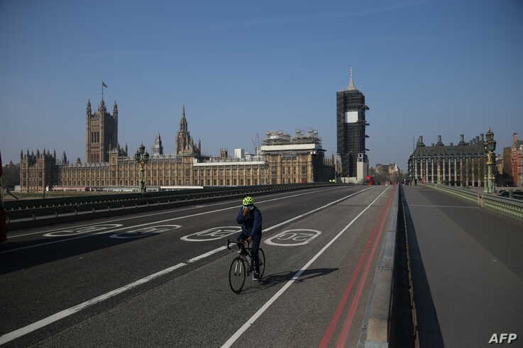 FILE - A cyclist crosses a near-empty Westminster Bridge with the Houses of Parliament in the background, amid the coronavirus outbreak, in central London, Britain, April 9, 2020.