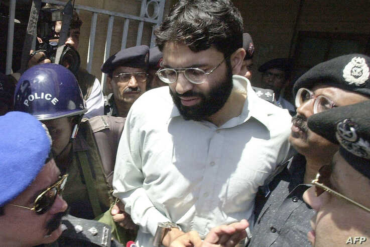 FILE - Pakistani police escort Ahmed Omar Saeed Sheikh, who was convicted in the 2002 killing of American journalist Daniel Pearl, as he exits a court in Karachi, Pakistan, March 29, 2002.