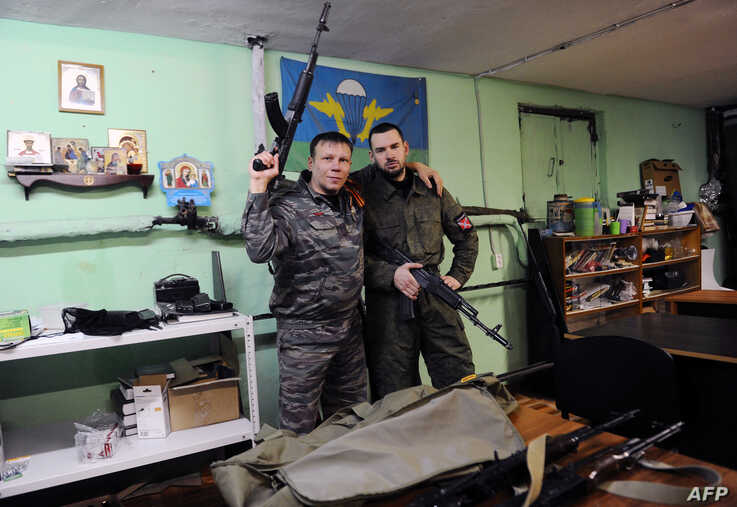 "FILE - Members of the ""Russian Imperial Movement"", a nationalist group in Russia, Dmitry Gaydun and Sergei Zinchenko pose for a picture with weapon simulators at a training base in Saint-Petersburg, Feb. 28, 2015."