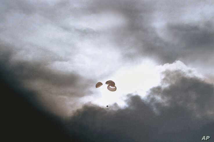 FILE - In this April 17, 1970, photo made available by NASA, the command module carrying the Apollo 13 crew parachutes to a splashdown in the Pacific Ocean.
