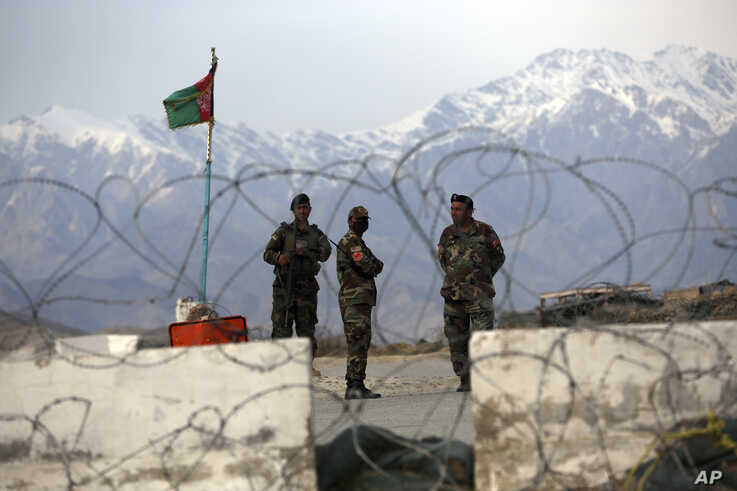 FILE - Afghan National Army soldiers stand guard at a checkpoint near the Bagram base in northern Kabul, Afghanistan, April 8, 2020.