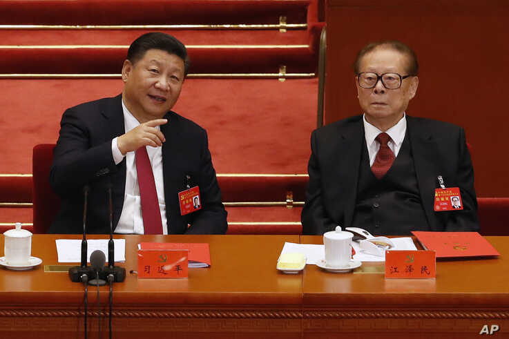 FILE - Chinese President Xi Jinping, left, chats with former President Jiang Zemin during the closing ceremony for the 19th Party Congress at the Great Hall of the People in Beijing, Oct. 24, 2017.