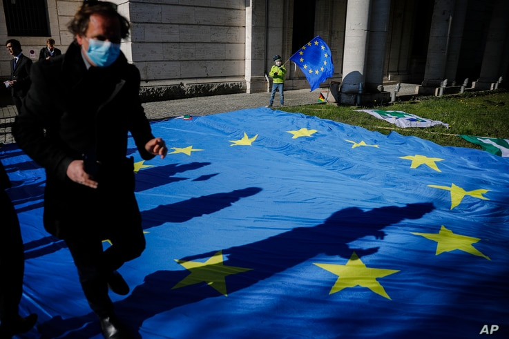 FILE - A man with a face mask and a child with an EU flag are seen at an event to garner more support for Italy during the coronavirus pandemic, in front of the Italian embassy in Berlin, Germany, April 22, 2020.
