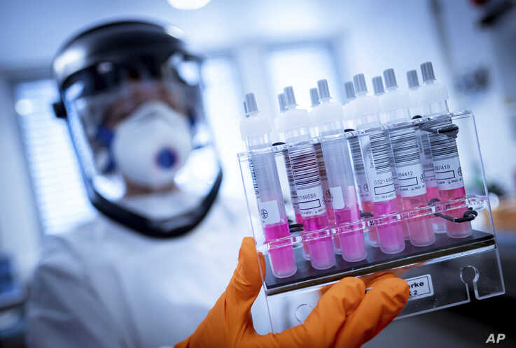 A research assistant holds coronavirus test samples in her hands at the Lower Saxony State Office for Consumer Protection and Food Safety (LAVES) in Hanover, Germany, April 1, 2020.