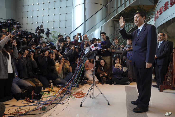 FILE - Newly-appointed head of China's liaison office in Hong Kong, Luo Huining, right, waves as he arrives for a media briefing at China's liaison office in Hong Kong, Jan. 6, 2020.