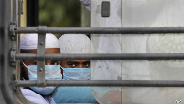 FILE - Indian Muslims wait in a bus to be taken to a coronavirus quarantine facility, in the Nizamuddin area of New Delhi, India, March 31, 2020.
