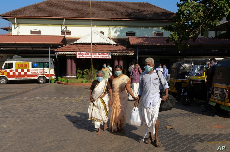Indians wearing surgical masks walk out of the government general hospital where a student who had been in Wuhan is kept in isolation in Thrissur, Kerala state, Jan. 30, 2020.