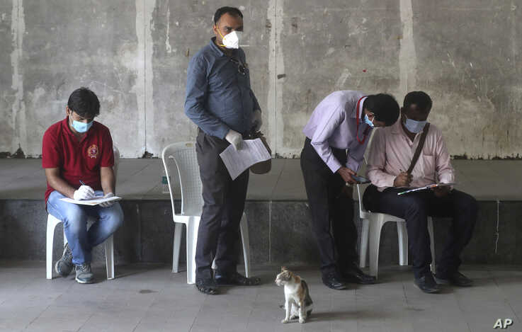 FILE - Indian journalists fill out forms for a swab test during a lockdown to control the spread of the coronavirus, in Mumbai, India, April 16, 2020.