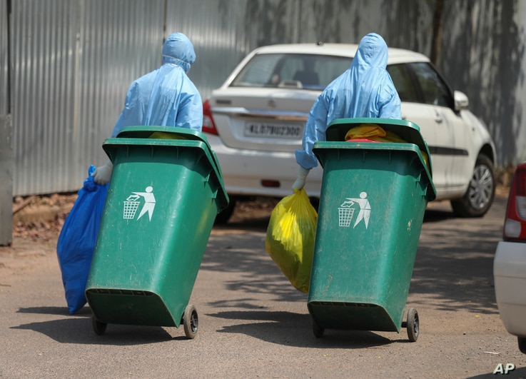 Indian workers walk with garbage after cleaning an isolation ward at a hospital for observing people suspected to have a new coronavirus infection in Kochi, Kerala state, Feb.4, 2020.