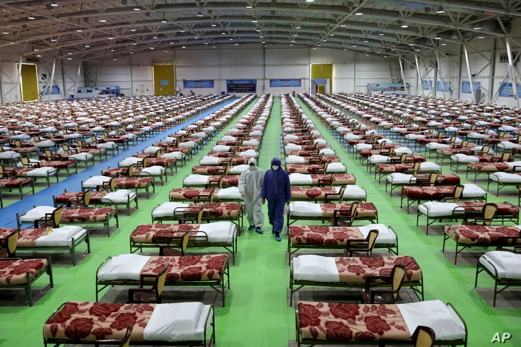 Men in protective gear walk past rows of beds at a temporary 2,000-bed hospital for coronavirus patients set up by the Iranian army, at an exhibition center in northern Tehran, Iran, March 26, 2020.