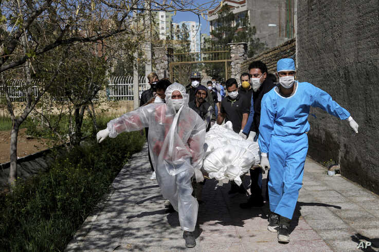 People wearing protective clothing carry the body of a victim who died after being infected with the new coronavirus, at a cemetery just outside Tehran, Iran, March 30, 2020.