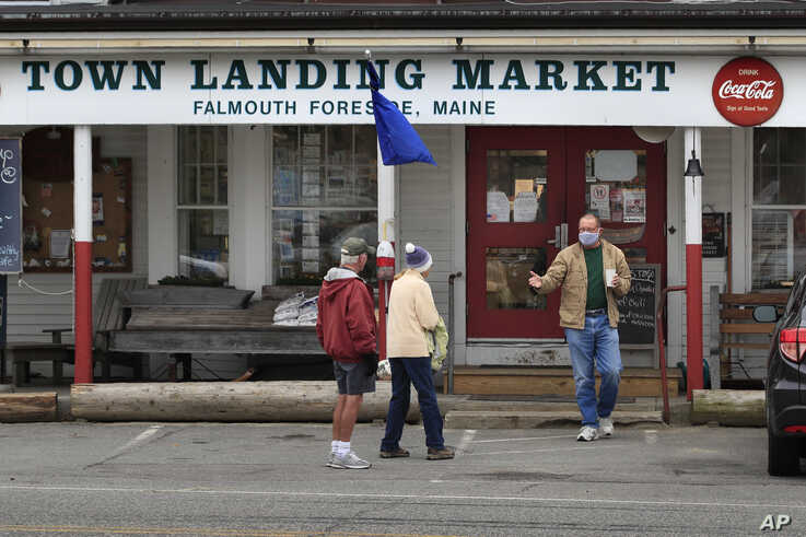 FILE - Customers chat outside the Town Landing Market in Falmouth Foreside, Maine, April 9, 2020, as the town's streets are empty due to the coronavirus pandemic.