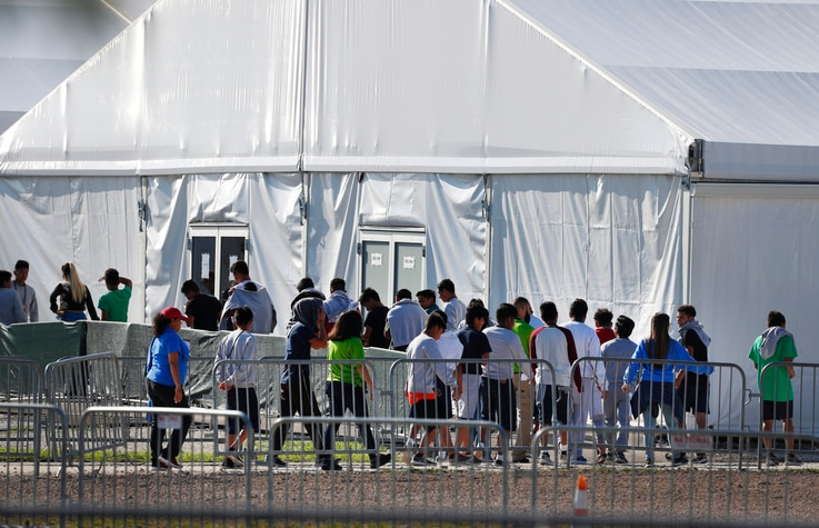 FILE - Detained migrant children from Central America line up to enter a tent at the Homestead Temporary Shelter for Unaccompanied Children in Homestead, Florida, Feb. 19, 2019.