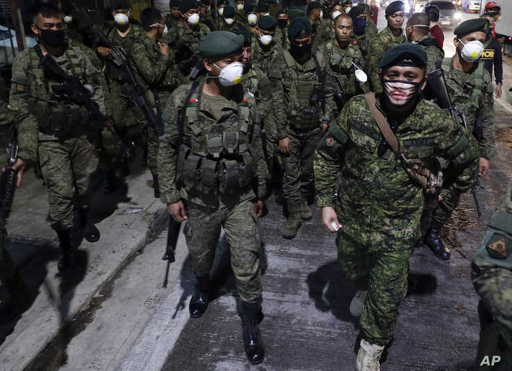 FILE - Filipino troopers wear protective masks as they arrive to augment police at Valenzuela, metropolitan Manila, Philippines, March 15, 2020.