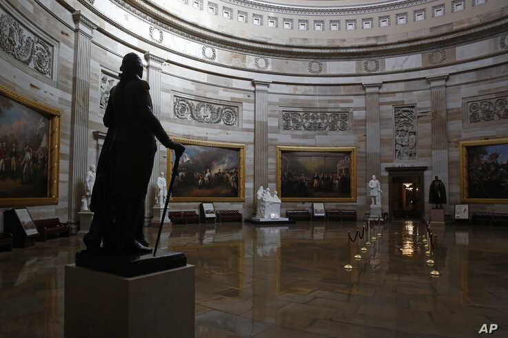 FILE - A statue of President George Washington looks over an empty Capitol Rotunda, on Capitol Hill in Washington, April 9, 2020.