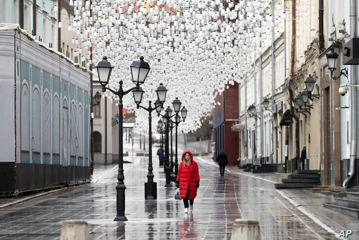A woman walks through an almost empty pedestrian street in Moscow, Russia.