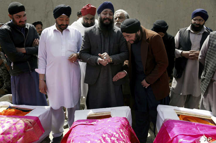 FILE - Afghan Sikh men mourn fellow believers killed by an Islamic State gunman, during their funeral in Kabul, Afghanistan, March 26, 2020.