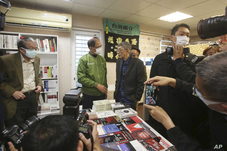 Lam Wing-kee, center right, one of five shareholders and staff at the Causeway Bay Book shop in Hong Kong, is congratulated by Taiwan's Legislative Yuan Speaker Yu Shyi-kun, center left, on the opening day of his new book shop in Taipei, April 25, 2020.