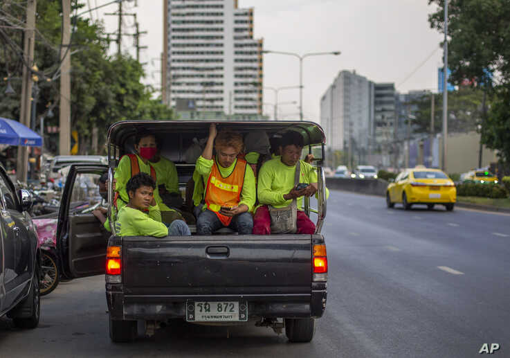 FILE - Migrant construction workers, some wearing face masks to protect against the coronavirus, are seen in a truck after concluding a day's work in Bangkok, Thailand, April 9, 2020.