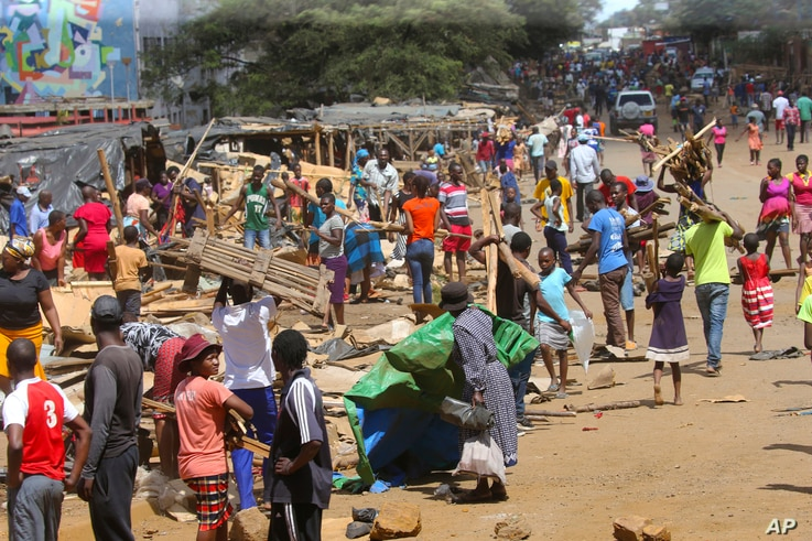 People clear destroyed stalls in the area of a popular market in a campaign to clean up the city, in Harare, Zimbabwe, April 18, 2020.
