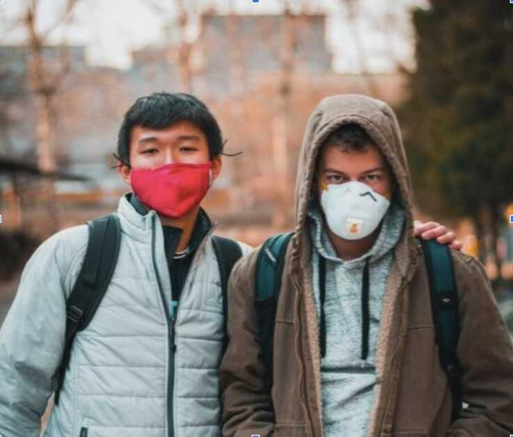 Two young men cover their faces with masks during the coronavirus pandemic. (Photo courtesy of Nico Zviovich)