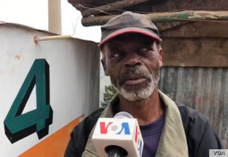 This man is not wearing a mask even though he knows he should. He says it takes getting used to and he finds it harder to breathe when he has it on. (Photo: Matiado Vilme / VOA)