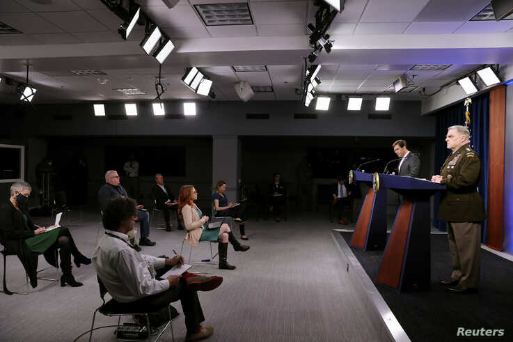 FILE - Members of the news media observe 'social distancing' as U.S. Defense Secretary Mark Esper and Joint Chiefs Chairman Army Gen. Mark Milley hold a news conference at the Pentagon in Arlington, Virginia, April 14, 2020.
