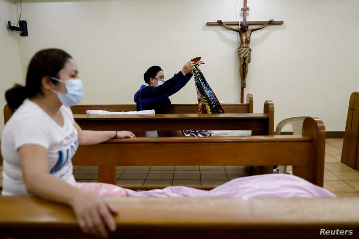 FILE - Hospital workers wearing protective masks prepare to sleep on pews at a funeral chapel that serves as a temporarily shelter for them amid the coronavirus spread, in Makati City, Metro Manila, Philippines, April 1, 2020.