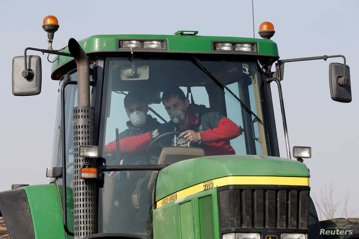 A French farmer, wearing a protective face mask, gives a driving lesson to a new young farm worker for his tractor in Anneux, France, March 27, 2020.