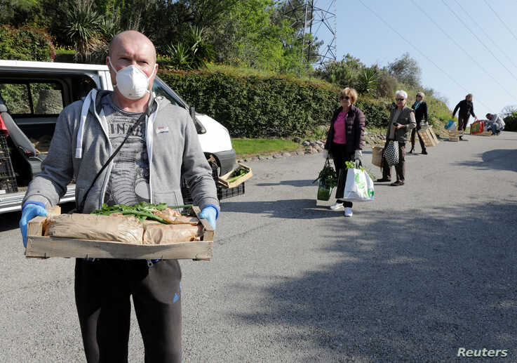 """Local residents practice social distancing as they shop fruits and vegetable directly from """"Le potager de Saquier"""" farm in Nice, France, as a lockdown is imposed to slow the rate of the coronavirus, April 3, 2020."""
