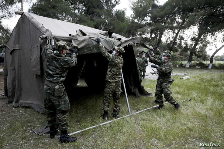 Greek army officers set up tents outside a hotel used as a shelter for refugees and migrants, after authorities found several cases of the coronavirus, in Kranidi, April 21, 2020.