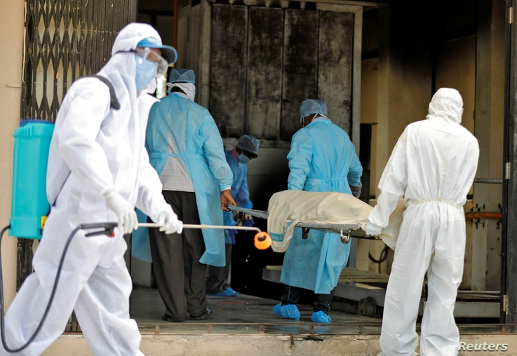 Municipal workers in protective gear carry the body of a woman who died of the coronavirus disease (COVID-19), to a crematorium in Ahmedabad, India, April 17, 2020.