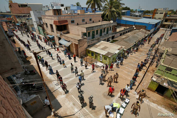 People stand on the lines by maintaining safe distance as they wait to receive free food being distributed by Central Reserve Police Force during a 21-day nationwide lockdown to slow the spreading of coronavirus in Chennai, India, April 1, 2020.