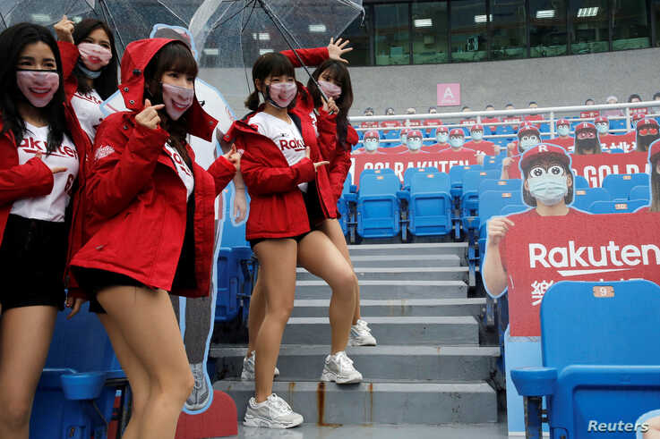 Cheerleaders take group photos with face masks on due to the outbreak of the coronavirus disease (COVID-19) at the first professional baseball league game of the season at Taoyuan International baseball stadium in Taoyuan city, Taiwan, April 11, 2020.