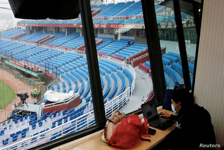 A reporter waits for the game to start at an empty stadium due to the coronavirus outbreak at the first professional baseball league game of the season at Taoyuan International baseball stadium in Taoyuan city, Taiwan, April 11, 2020.