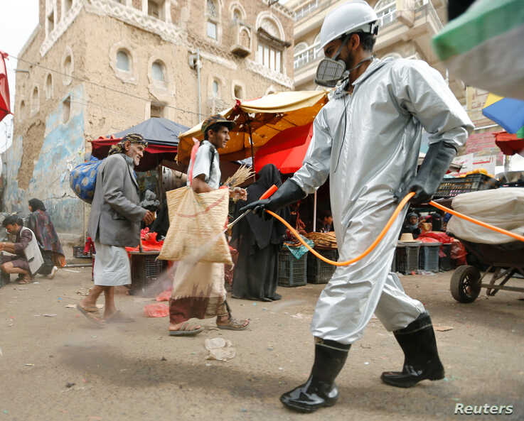 A health worker wearing a protective suit disinfects a market amid concerns of the spread of the coronavirus disease (COVID-19), in Sanaa, Yemen, April 28, 2020.
