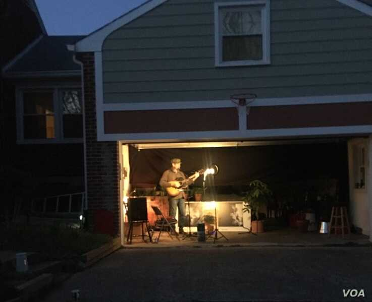 Bill Crandall plays guitar in his garage and shares his performance with neighbors and on social media, Takoma Park, Maryland. (M. Diallo/VOA)