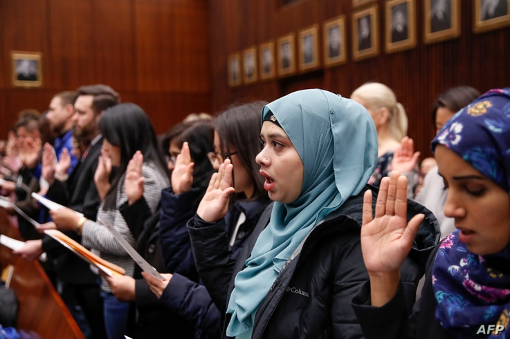Lila Mubarak (2nd R) takes the Oath of Allegiance during a naturalization ceremony at the Everett McKinley Dirksen United…