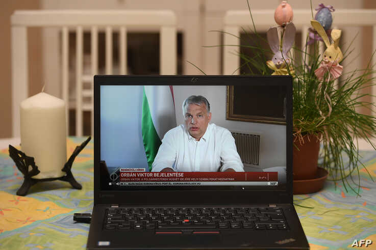 Hungarian Prime Minister Viktor Orban is seen on a laptop screen photographed in a flat in Budapest, as he makes an…