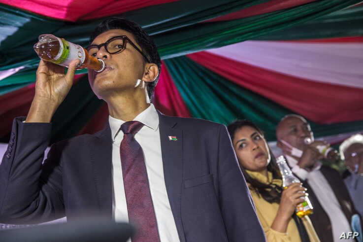 """Madagascar's President Andry Rajoelina drinks a sample of the """"Covid Organics"""" or CVO remedy at a launch ceremony"""
