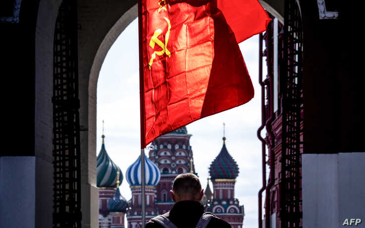 A Russian Communist party supporter carries a red flag as he walks along Red Square in Moscow on May 1, 2020. - The Labour Day…