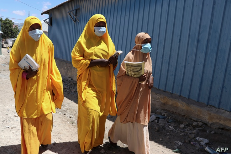 (FILES) In this file photo taken on March 19, 2020 Students walk in a Mogadishu neighbourhood wearing face masks as protective…