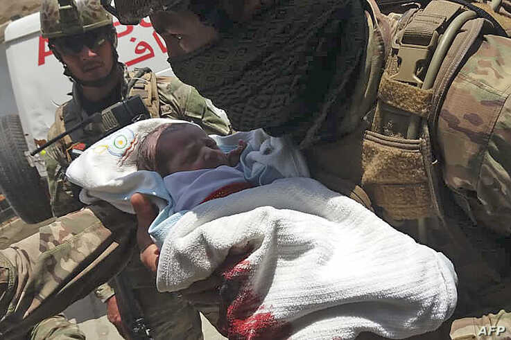 An Afghan security personnel carries a newborn baby from a hospital, at the site of an attack in Kabul on May 12, 2020. -…