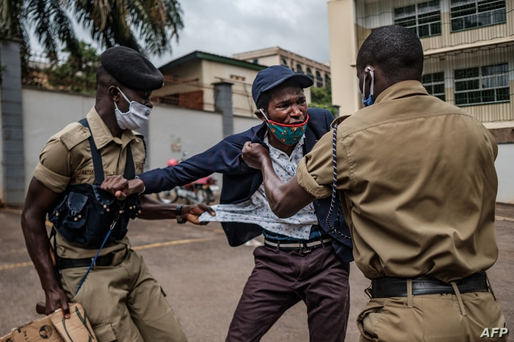A protester is arrested by police officers as Stella Nyanzi (not visible), a prominent Ugandan activist and government critic,…