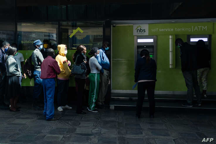 People queue for cash at an ATM which dispensed the new  Zimbabwean ten-dollar notes in Harare on May 20, 2020. - The Reserve…