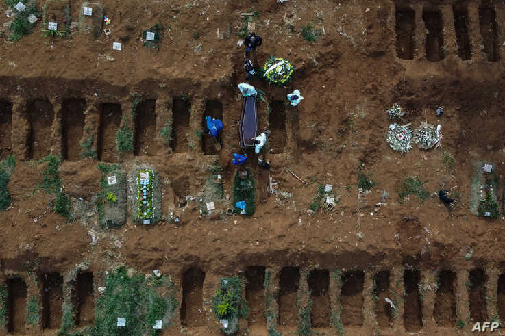 Aerial picture showing gravediggers burying an alleged COVID-19 victim at the Vila Formosa Cemetery, in the outskirts of Sao…